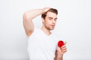 頭を触る男性の画像