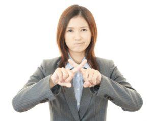 指で✖を作る女性