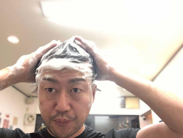 シャンプーで頭を洗う男性の画像