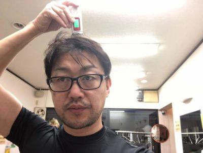 水分チェッカーで頭皮チェックする男性の画像