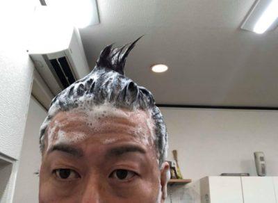 イクオスブラックシャンプーで頭を洗う男性の画像