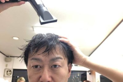 ドライヤーで頭を乾かす男性の画像