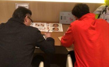 問診票を書く男性2人の画像