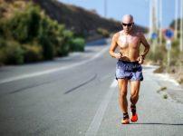 坊主で走る男性の画像
