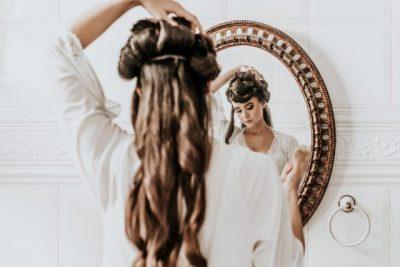 鏡の前で頭を触る女性の画像