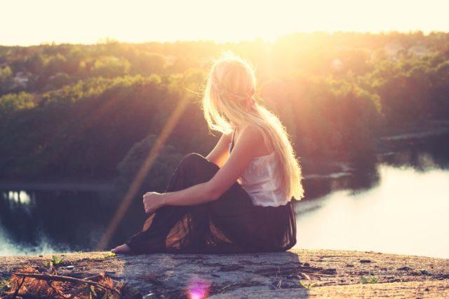 夕日をバックに座る女性